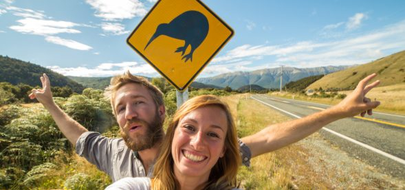 Kiwi couple in front of a kiwi sign
